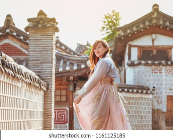 travel and tourist korea concept from beautiful woman in korea traditional cloth (hanbok) relax, take picture in vintage town with rim light and soft focus background