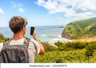 Travel tourist man in Hawaii beach USA vacation taking photo with mobile phone device of ocean landscape mountains background. Big Island, Hawaii.