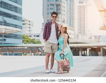 Travel tourist standing with luggage looking map in smartphone at the city. Travelers using gps map for sightseeing in town.Couple tourist walking with luggage and travel in city.Travel lifestyle.