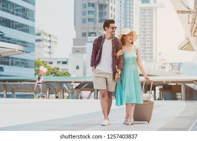Travel tourist standing with luggage looking map in smartphone at the city. 
