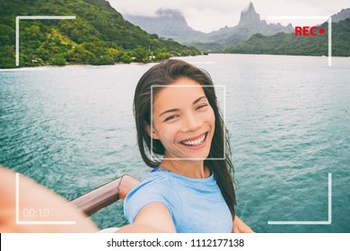 Travel tourist woman vlogging doing video vlog online during Tahiti luxury cruise vacation. Asian girl talking online doing video blog recording in Bora Bora island landscape.