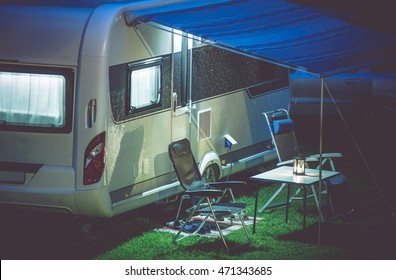 Travel Trailer Camping Romantic Setup. Modern Travel Trailer and Camping Furnitures Under the Awning. Modern Caravaning.