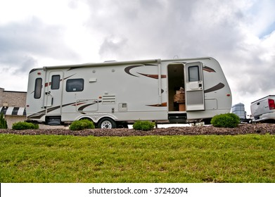 A travel trailer sits on a hill with the door open and a dog seated on the bed inside.