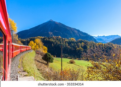 Travel with train of Rhaetian Railway in golden autumn through the line of Glacier Express in Engadin, Canton of Grisons, Switzerland.