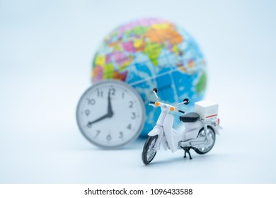 Travel and transport concept. Close up of miniature motercycle scooter model figure with vintage round clock and mini world ball on white background.