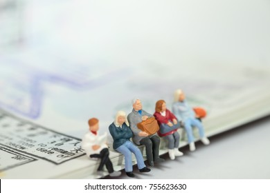 Travel and transport concept. Group of traveller miniature figures sitting and waiting on passport with immigration stamps.