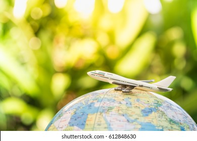 Travel and transport concept. Toy airplane on world map balloon with green nature as background.