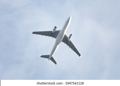 Travel, transportation, aviation concept, copy space/ Wide-body passenger airplane  flying overhead against a spring blue sky, bottom view