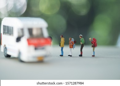 Travel and transportation Concept. Close up of group of traveler miniature figure with backpack standing with mini toy van model.