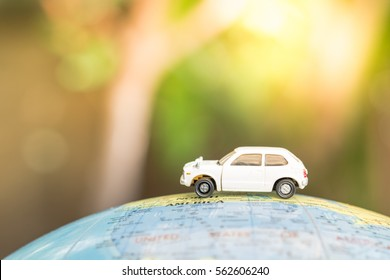 Travel and Transportation concept. White toy car on world map balloon.