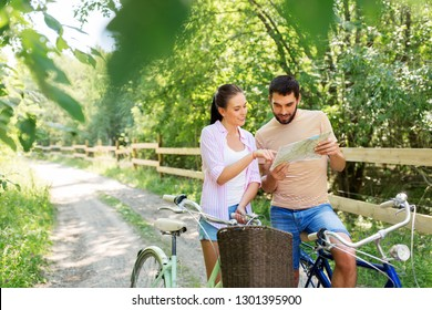 travel, trip, leisure and lifestyle concept - happy young couple with map and bicycles looking for location at country in summer