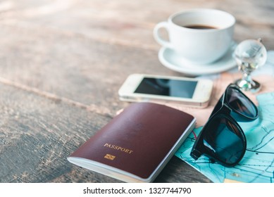 Travel , trip vacation, tourism mockup - close up of compass, glass of water note pad, pen and toy airplane and tourist map on wooden table. Empty space you can place your text or information.