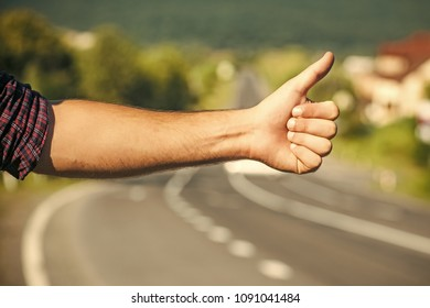 Travel, trip, vacation, wanderlust. Hitchhiker sign on road. Thumbs up male hand gesture outdoors. Hitchhiking, hitching, thumbing auto stop concept