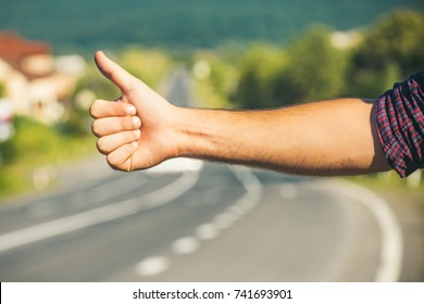 Travel, trip, vacation, wanderlust. Hitchhiker sign on road. Thumbs up male hand gesture outdoors. Hitchhiking, hitching, thumbing, auto stop concept.