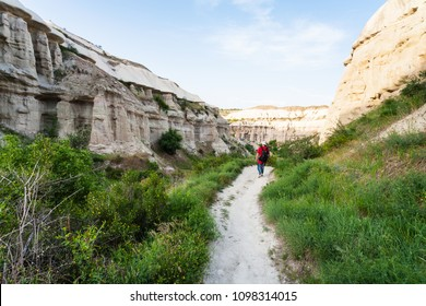 Travel to Turkey - tourist walks along pathway near Goreme town in Cappadocia in spring