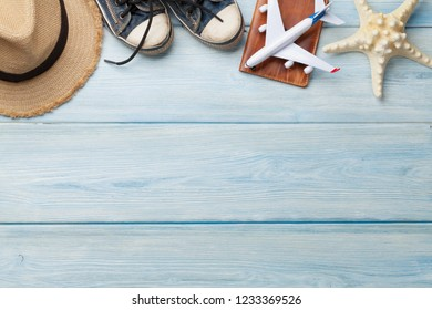 Travel vacation background concept with beach hat, passport and airplane toy on wooden backdrop. Top view with copy space. Flat lay