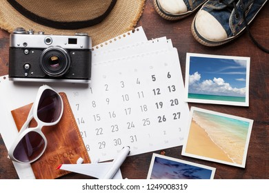 Travel vacation background concept with calendar, sun hat, camera, passport, airplane toy and weekend photos on wooden backdrop. Top view. Flat lay. All photos taken by me
