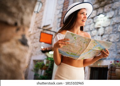 Travel vacation city concept. Young happy traveler woman with map walking