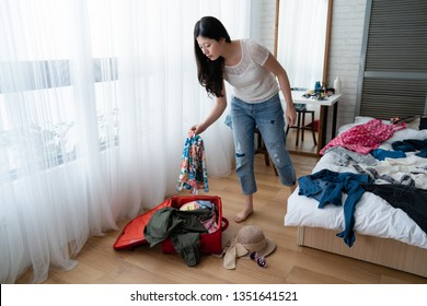 Travel and vacation concept. happy asian woman packing stuff and clothes into suitcase on wooden floor prepare for her travel and journey trip. full length young girl standing bedroom mirror in back