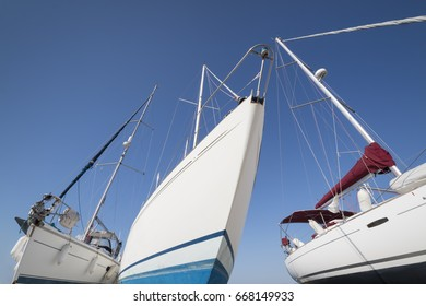travel or vacation concept with three white  sailing yachts at the boatyard  in front of a blue sky