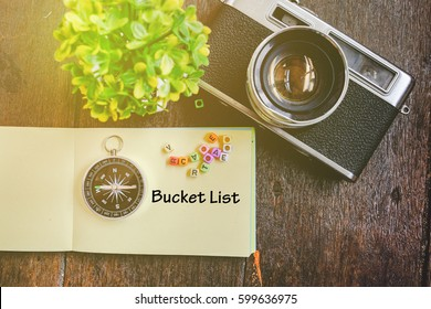 Travel and vacation concept, word BUCKET LIST, vintage camera, compass and artificial plant on wooden background