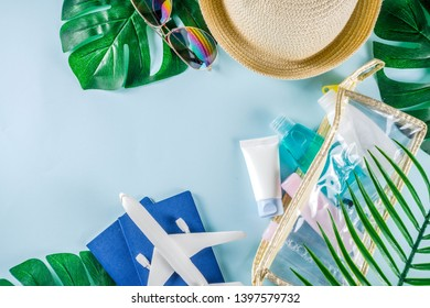 Travel and vacation flatlay concept. Summer bright colorful background with hat, sunglasses, plane,  passport, tropical leaves, travel cosmetics kit, seashells, copy space top view banner