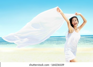 Travel and Vacation. Freedom Concept. Beautiful Girl With White Scarf on The Beach enjoying summer.