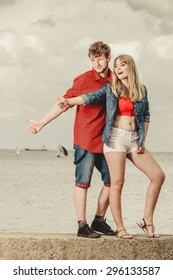 Travel vacation hitchhiking concept. Young smiling couple thumbing and hitch hiking by seaside outdoor