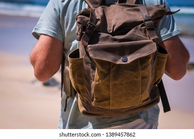 Travel and vacation lifestyle concept with man and leather vintage backpack viewed from rear - sku and beach in background for outdoor leisure activity people