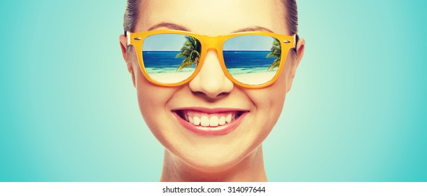 travel, vacation, summer holidays and happy people concept - portrait of happy teenage girl in sunglasses with beach reflection