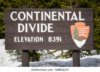 Travel vacation tourism photos taken in Wyoming USA continental divide sign on mountain buried covered in snow.