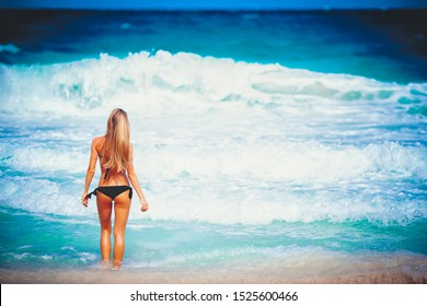Travel vacation widescreen wallpaper - Beautiful young pretty blonde girl in bikini white sand on perfect sport sexy body relax in sea waves of white sand paradise tropical beach at wind storm day