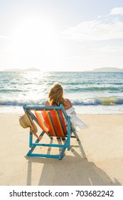 Travel vacation woman relaxing  on sun bed sofa lounge chair on holidays at the tropical beach