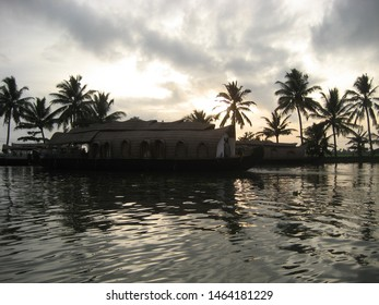 Travel view of Kerala houseboats featuring canal houseboat palms clouds. The image location is Kerala in India, Asia.