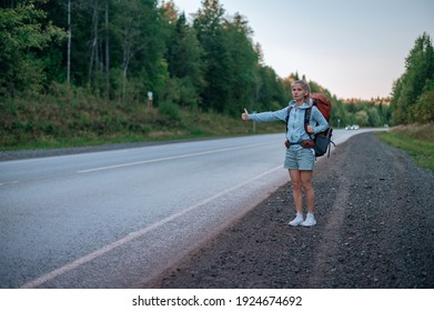 Travel woman with backpack hitchhiking on road.