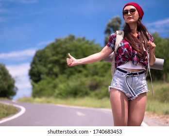 Travel woman hitchhiking  with backpack and red hat. A female hitchhiker by the road during vacation trip.The concept of traveling and hitchhiking.