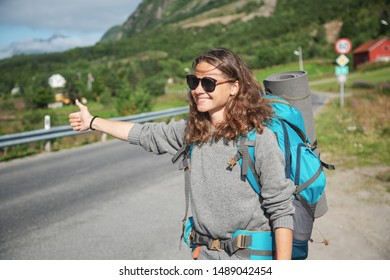 Travel woman hitchhiking. Backpacker on road. Happy smiling gorl with big backpack