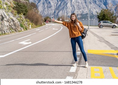 Travel woman hitchhiking. Beautiful young female hitchhiker by the road during vacation trip in mountains Montenegro