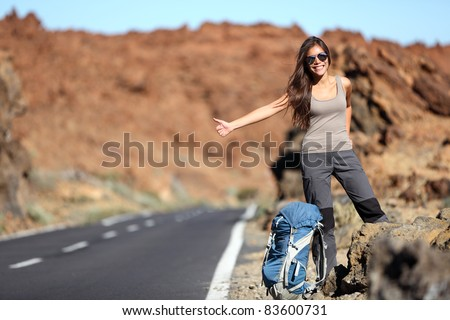 Travel woman hitchhiking. Beautiful young female hitchhiker by the road during vacation trip on Volcano Teide, Tenerife, Canary Islands.