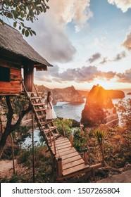 Travel woman looking sunrise view Tree House with Daimond  beach, Nusa Penida island Bali ,Indonesia