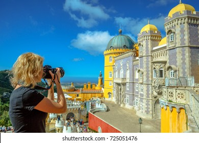 Travel woman photographer takes photos of Pena National Palace. Female photographer with professional camera takes shot of the most visited attraction in Sintra, Portugal. Travel and tourism in Europe