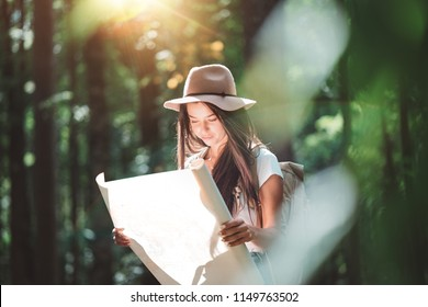 Travel woman reading map among trees at forest and searching directional for travling with a backpack