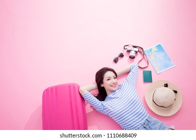 travel woman smile happily and lying on pink floor