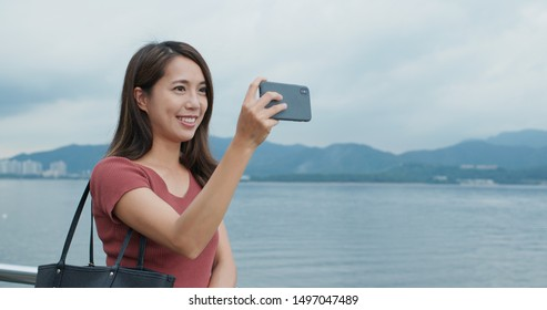 Travel woman use of mobile phone for take photo at outdoor