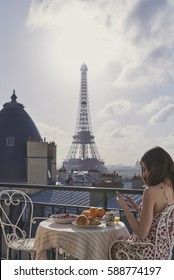 Travel woman view Eiffel Tower Paris smart phone technology social media hotel terrace breakfast destination vacation