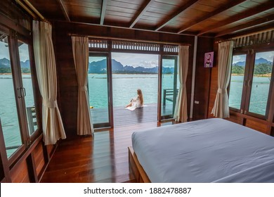 Travel Woman in White Dress Sitting Outdoor near Wooden House on Water. View on Tourist Woman Relaxing and Leisure from Raft House on Cheow Lan Lake in Thailand. Eco Tourism