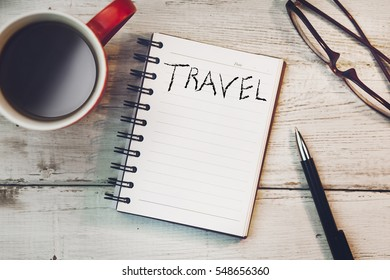 travel word on notebook with coffee on a wooden table
