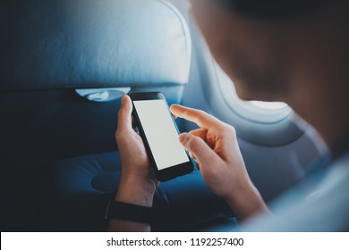 Travel the world. Back view of young man using modern smartphone in airplane, hipster guy holding cellphone with blank screen for text message or design, business travel, businessman in aircraft