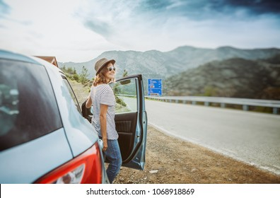 Travel - young beautiful hipster woman in hat travel by car, rent a car in vacations, image with retro tone