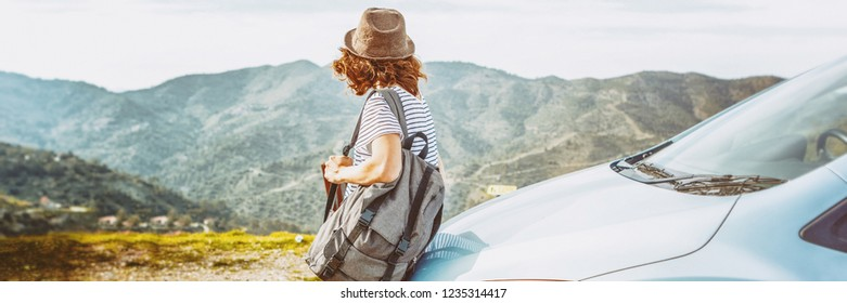 Travel - young beautiful hipster woman in hat travel by car, rent a car in vacations, banner panorama